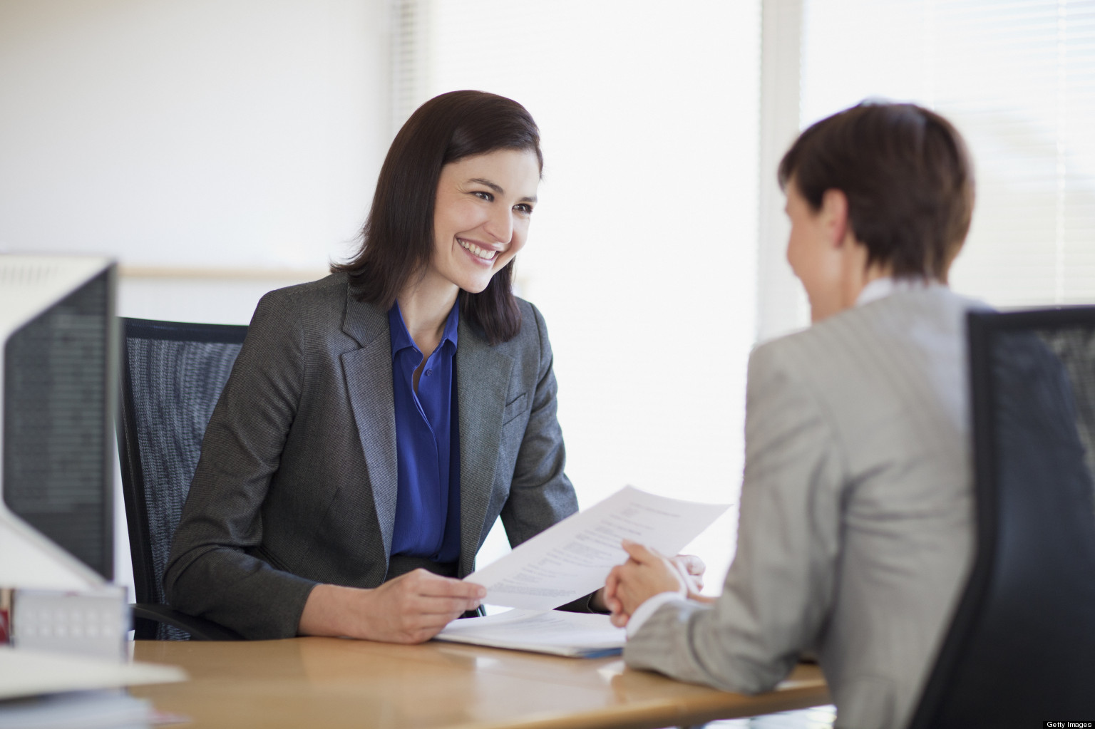 Businesswomen with paperwork talking face to face
